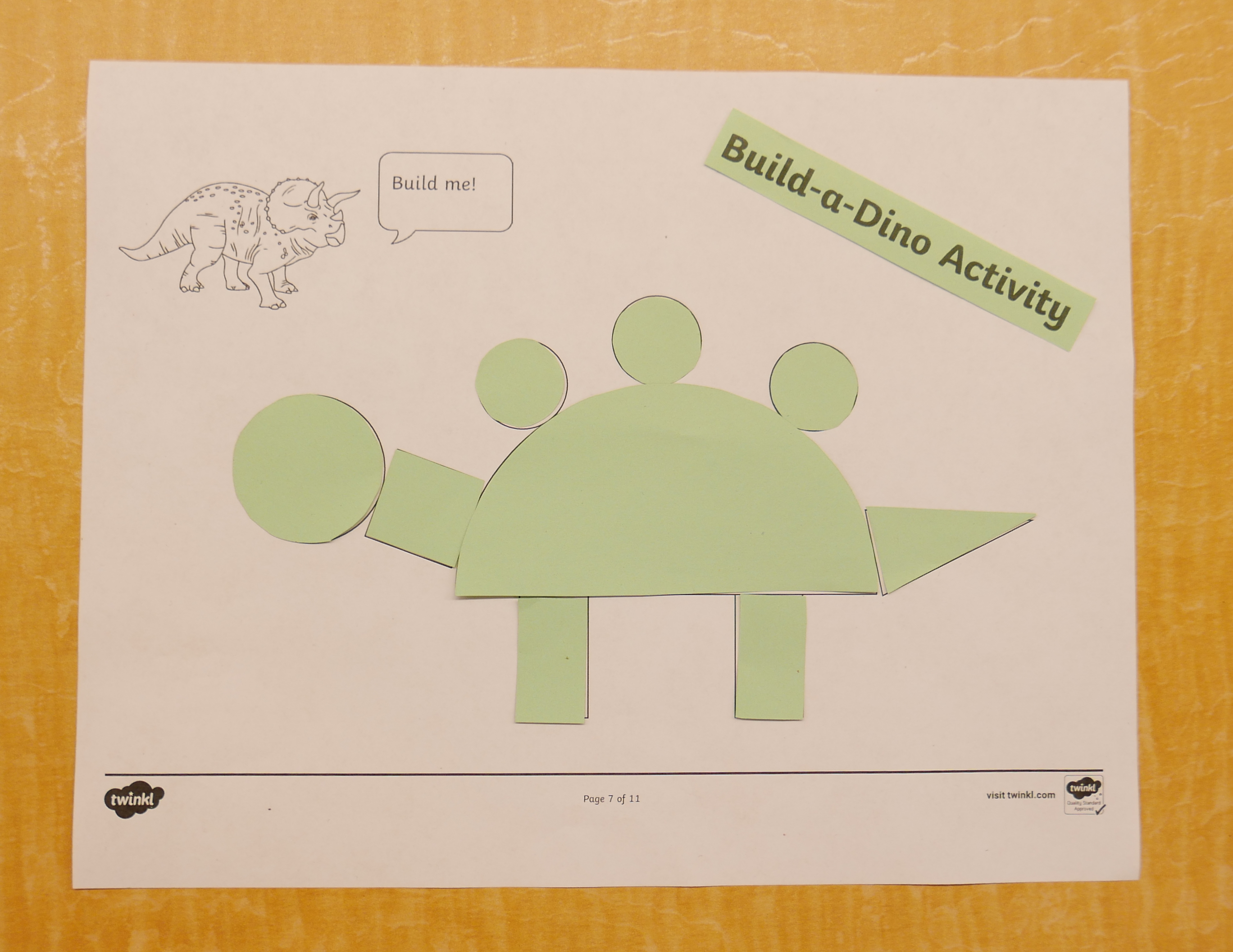 shapes put together in green paper on white paper that look like a dinosaur
