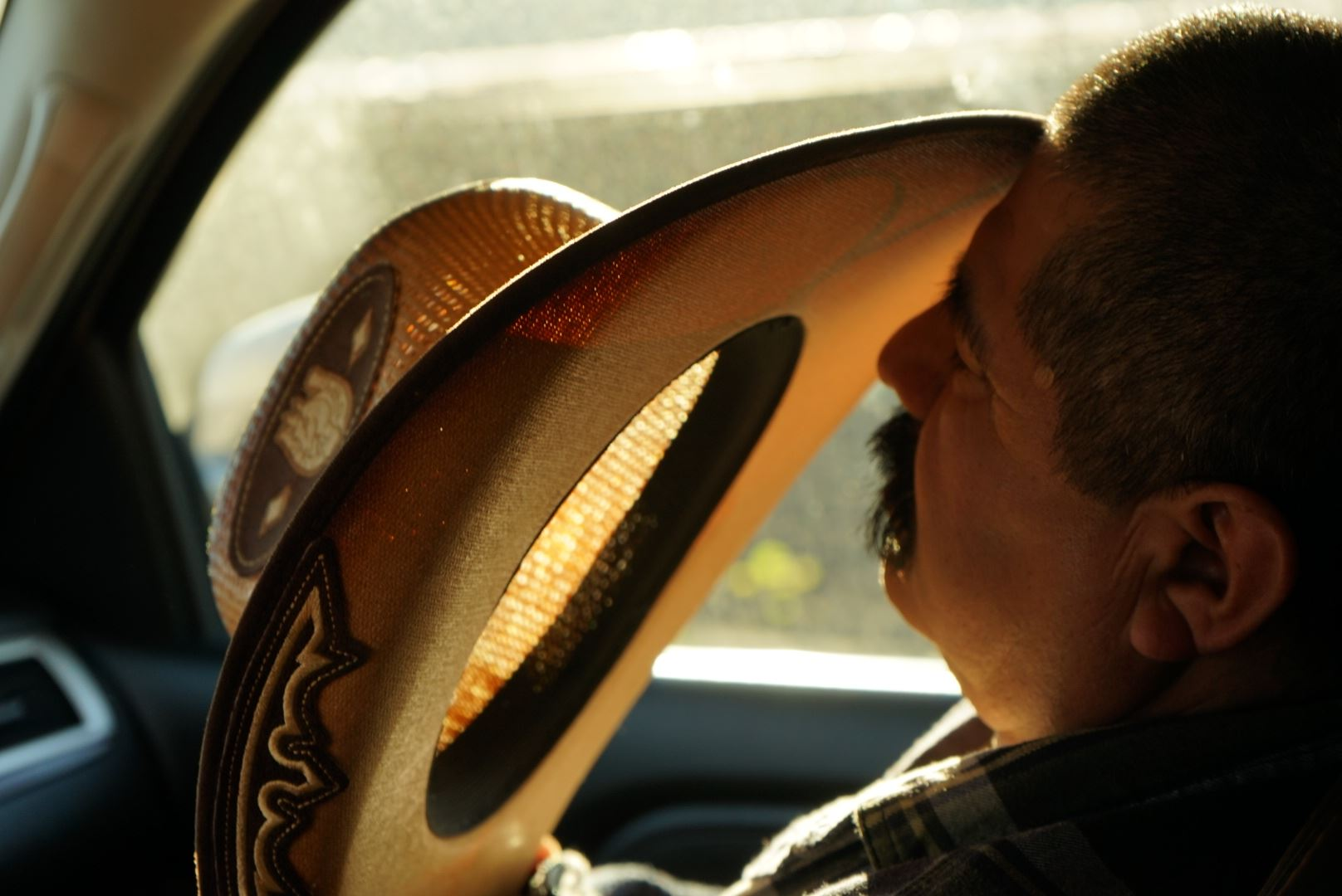 photograph of a man asleep in a car with his hat resting against his forehead