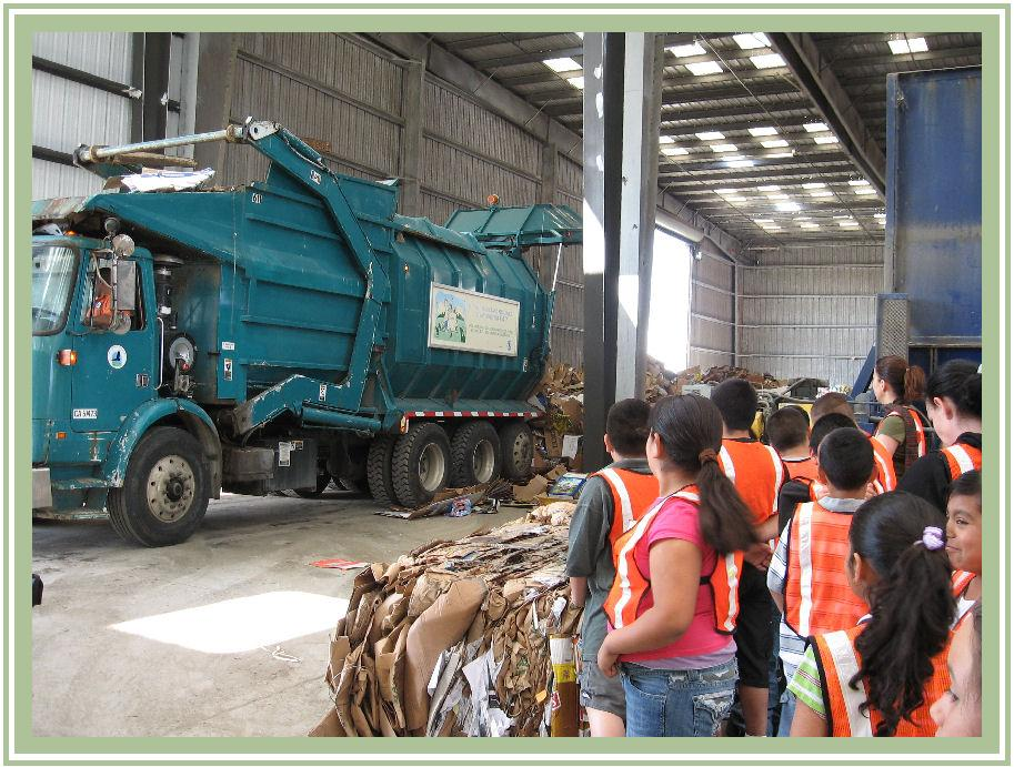 Student in warehouse viewing a recycling truck