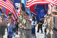 Boy Scouts holding flags walking in a parade