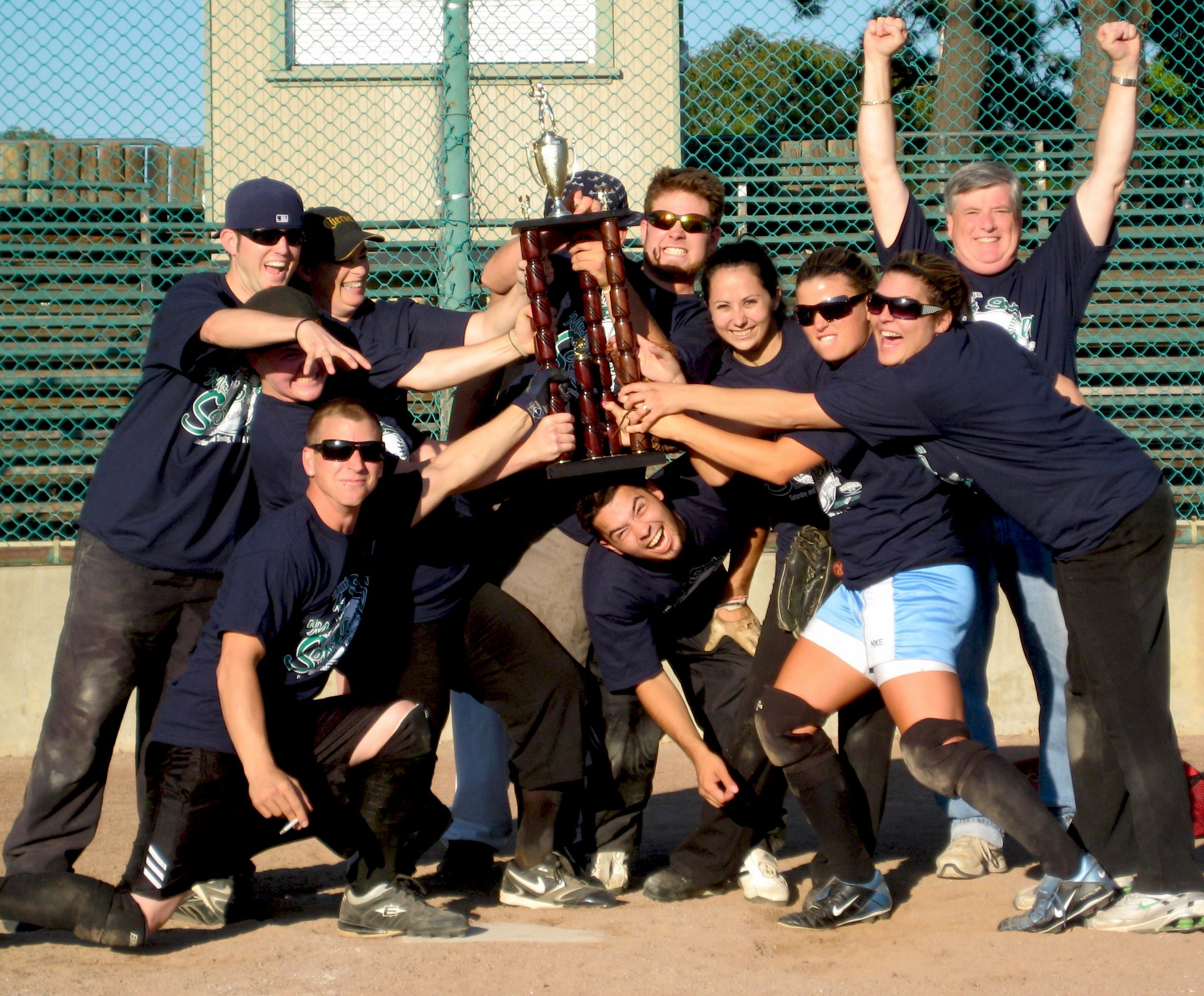 Co-ed softball team posing with trophy