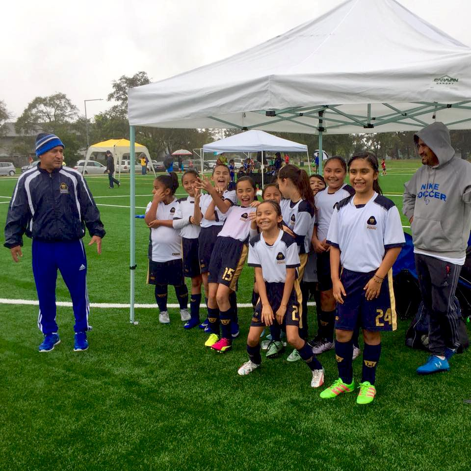 Female youth soccer participants in uniform under a canopy
