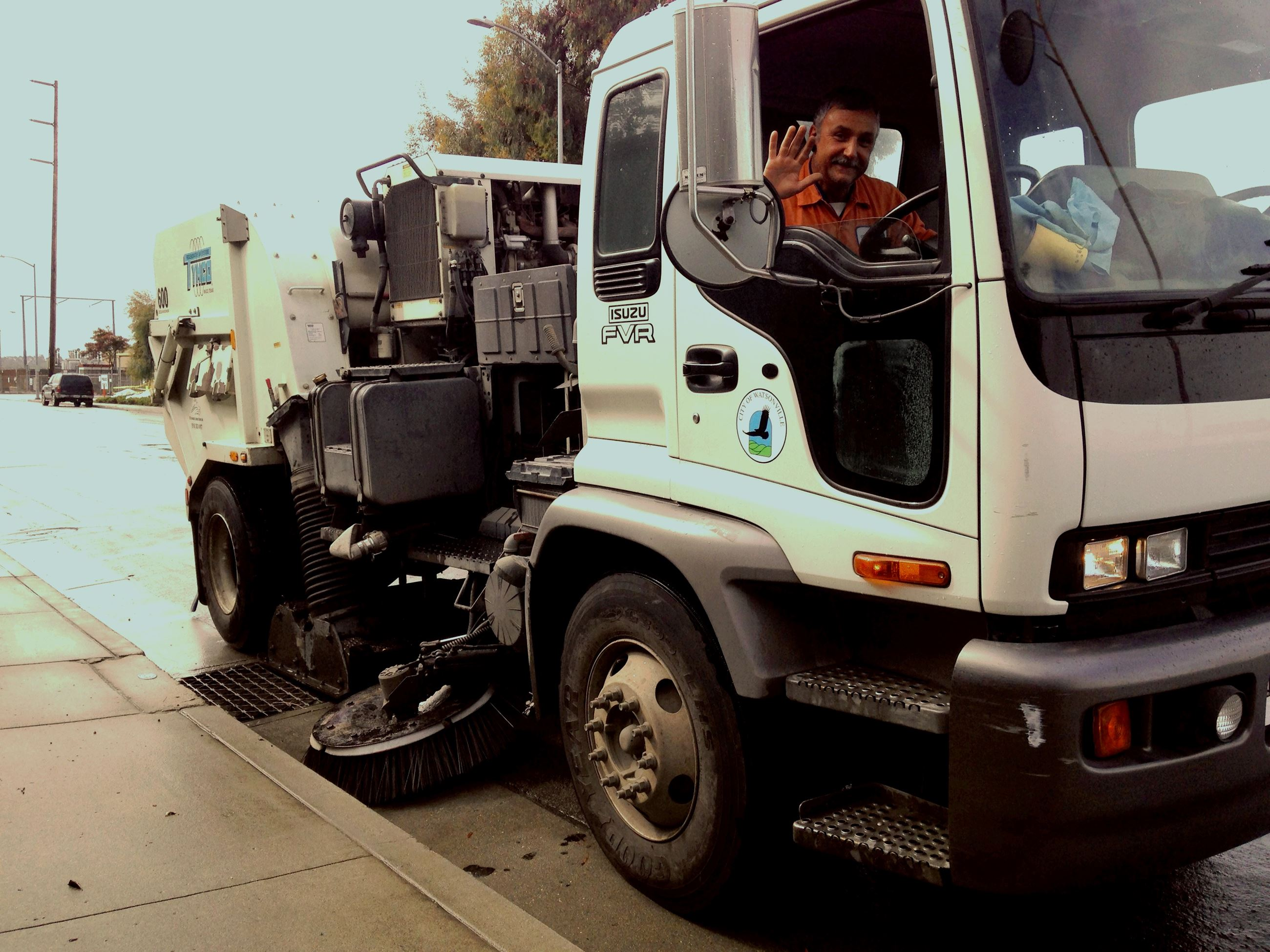 Street sweeper driver waving from truck