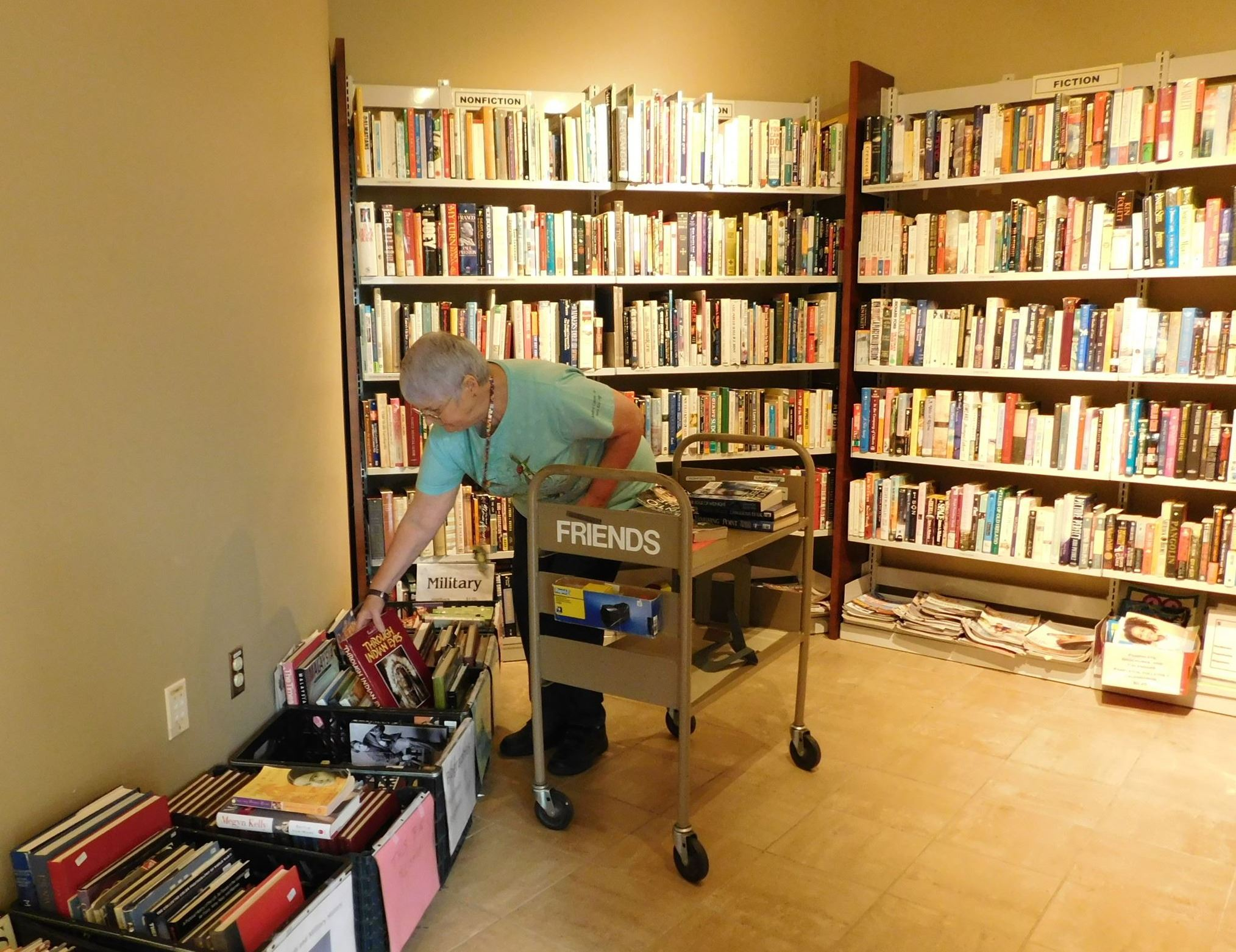 woman volunteer setting items into the friends of the library bookstore